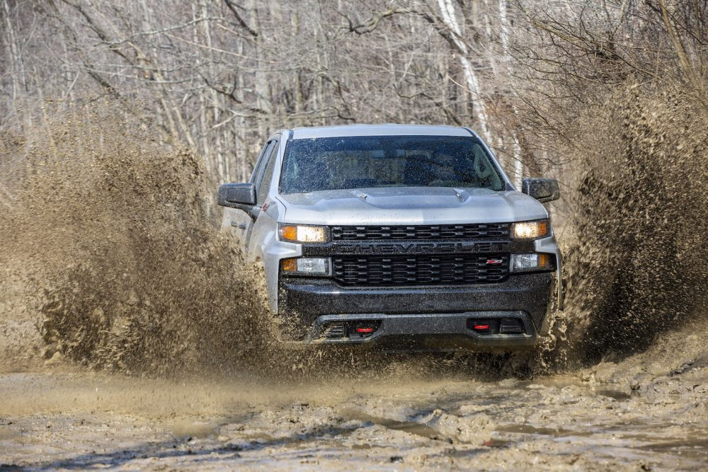 The Chevrolet Silverado Trail Boss crashing into mud puddles on the edge of a wooded area