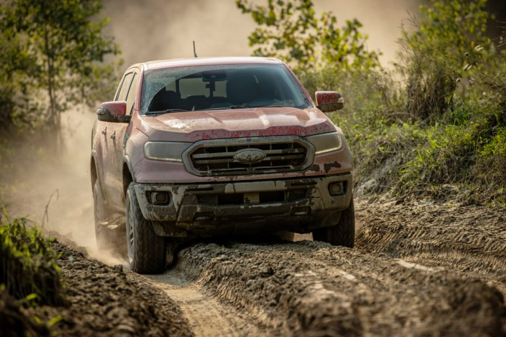 2021 Ford Ranger Tremor Lariat with mud on the front driving on a trail