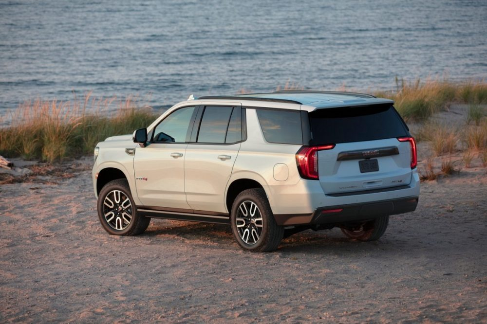Side and back view of the 2021 GMC Yukon AT4 SUV on a sandy cliff facing the ocean