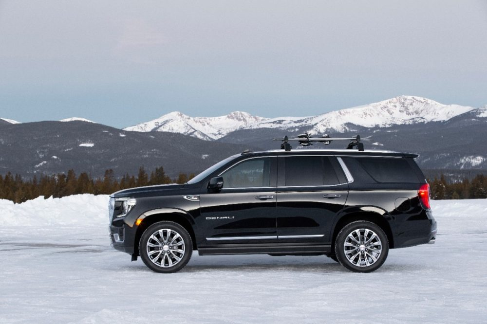 The 2021 GMC Yukon on the snow with mountains behind it