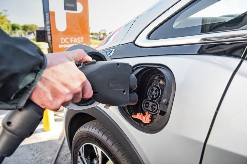 A person putting a charging cord into an EV