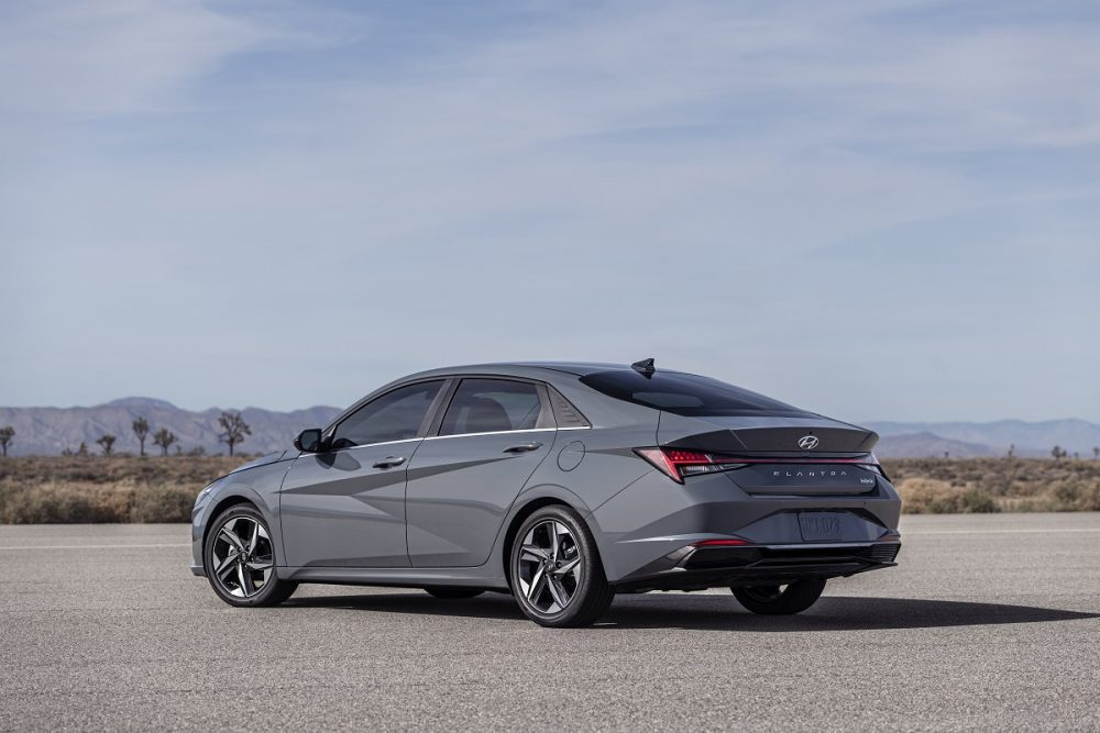 Rear side view of gray 2021 Hyundai Elantra Hybrid parked on asphalt with mountain and desert backdrop.