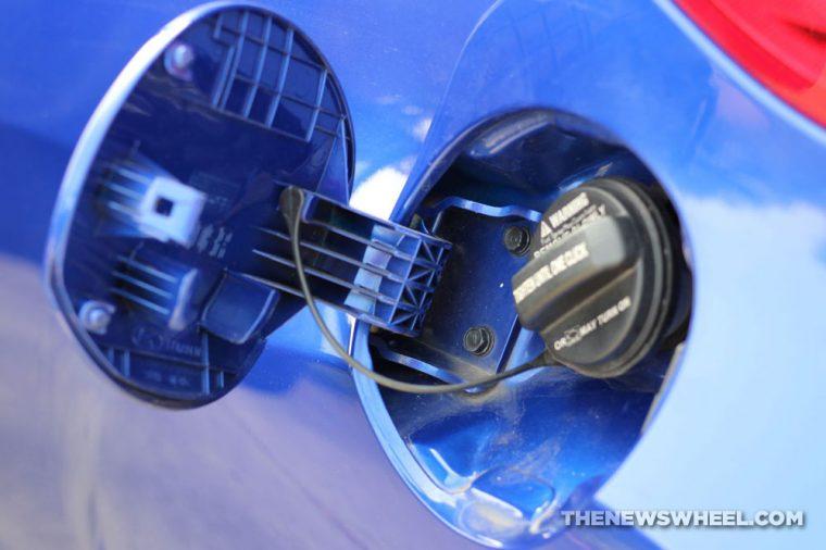 An open gar tank lid on a blue car