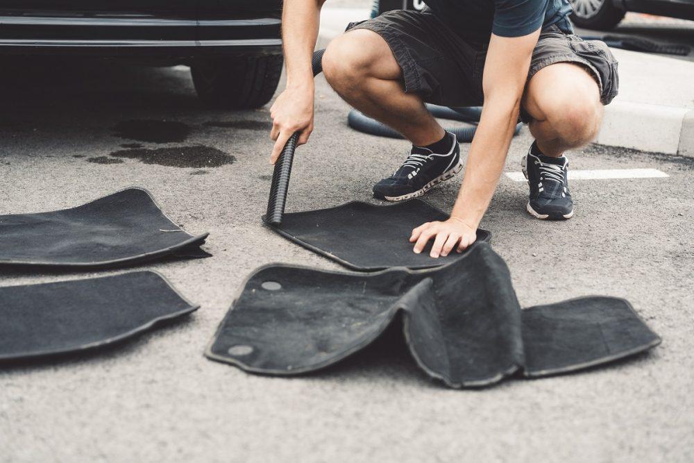 man vacuuming car floor mats