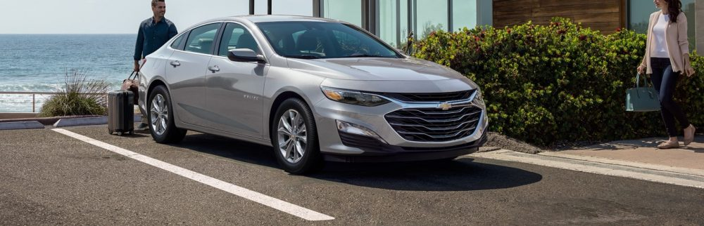 2021 Chevrolet Malibu parked by the a house in front of the ocean