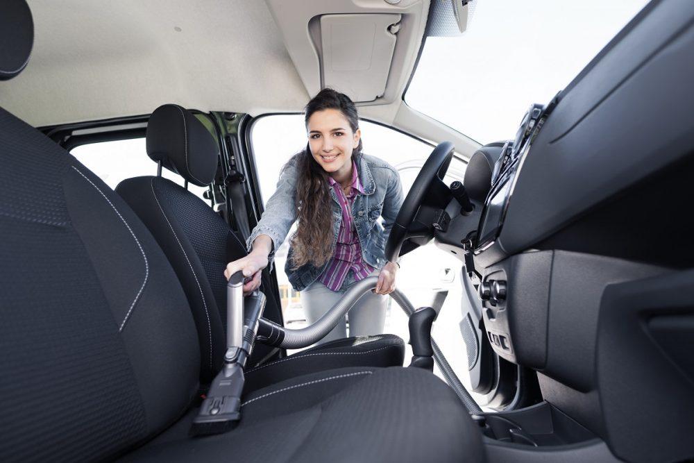 woman vacuuming car interior