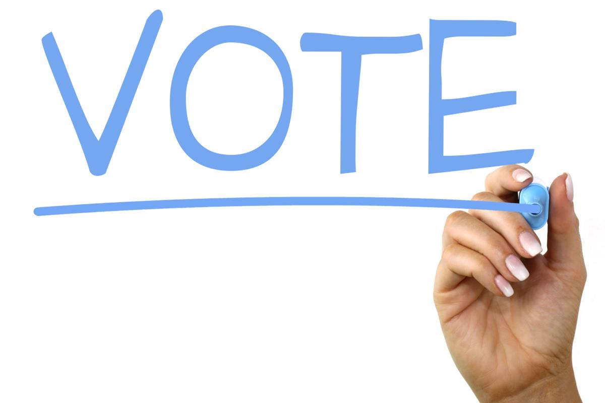 """A hand writing the word """"vote"""", which is all the ideal political bumper sticker would say."""