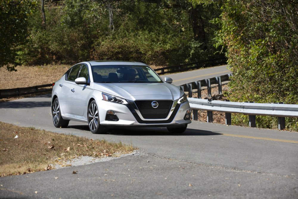Front view of 2021 Nissan Altima driving on windy paved road next to silver guard rail with trees in the background