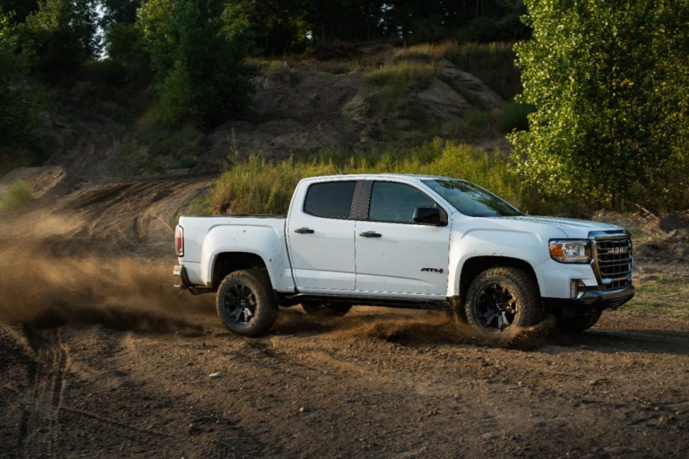 Side view of 2021 GMC Canyon AT4 Off-Road Performance Edition driving on dirt path