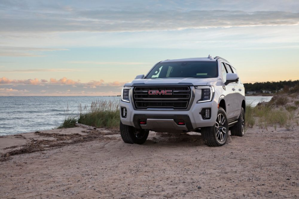 2021 GMC Yukon AT4 parked on sand by a lake or ocean