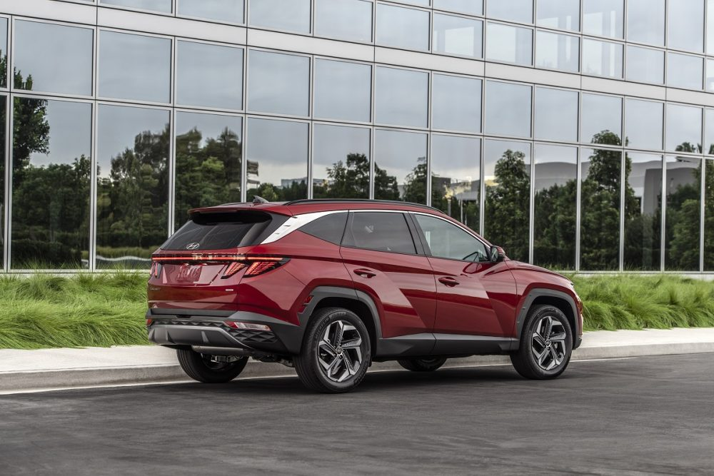 Rear side view of 2022 Hyundai Tucson parked in front of reflective windows