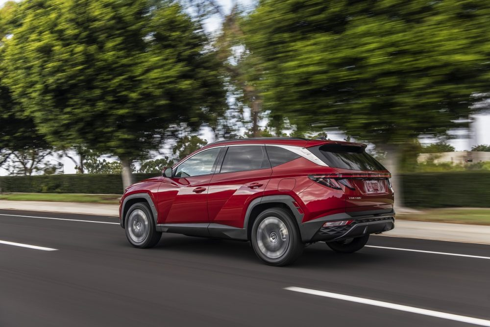 Rear side view of red 2022 Hyundai Tucson driving down road with trees in the background