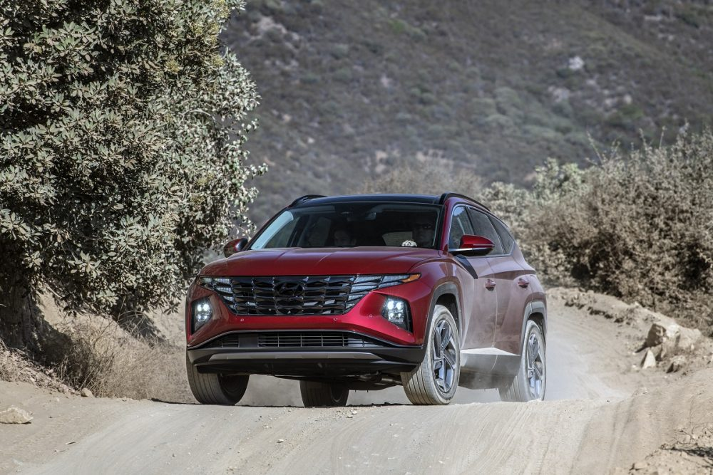 Front view of 2022 Hyundai Tucson driving on dusty mountain road