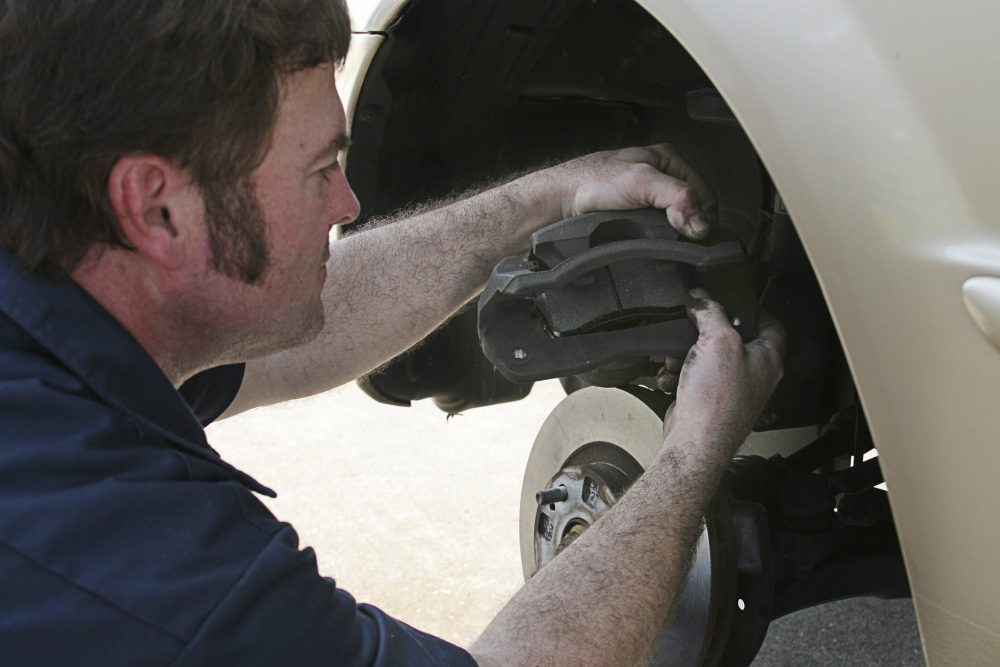Service technician looking at a vehicle's brake pads.