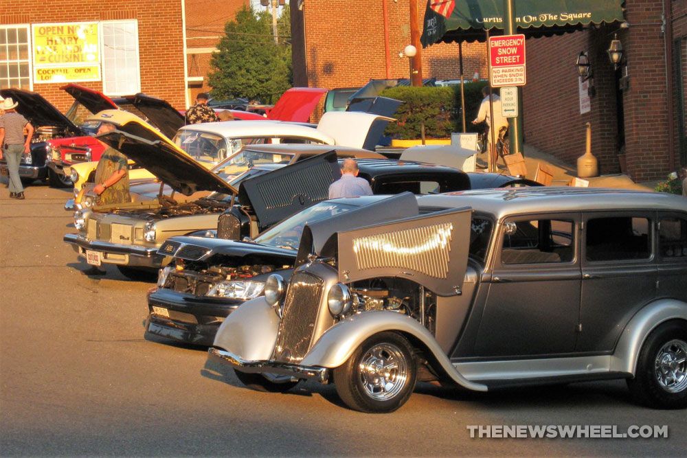 Classic cars show on city streets with hoods up and spectators walking