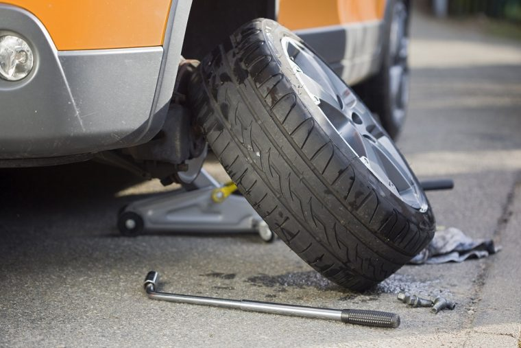 Tire Leaning Against Car with Jack and Tire Iron
