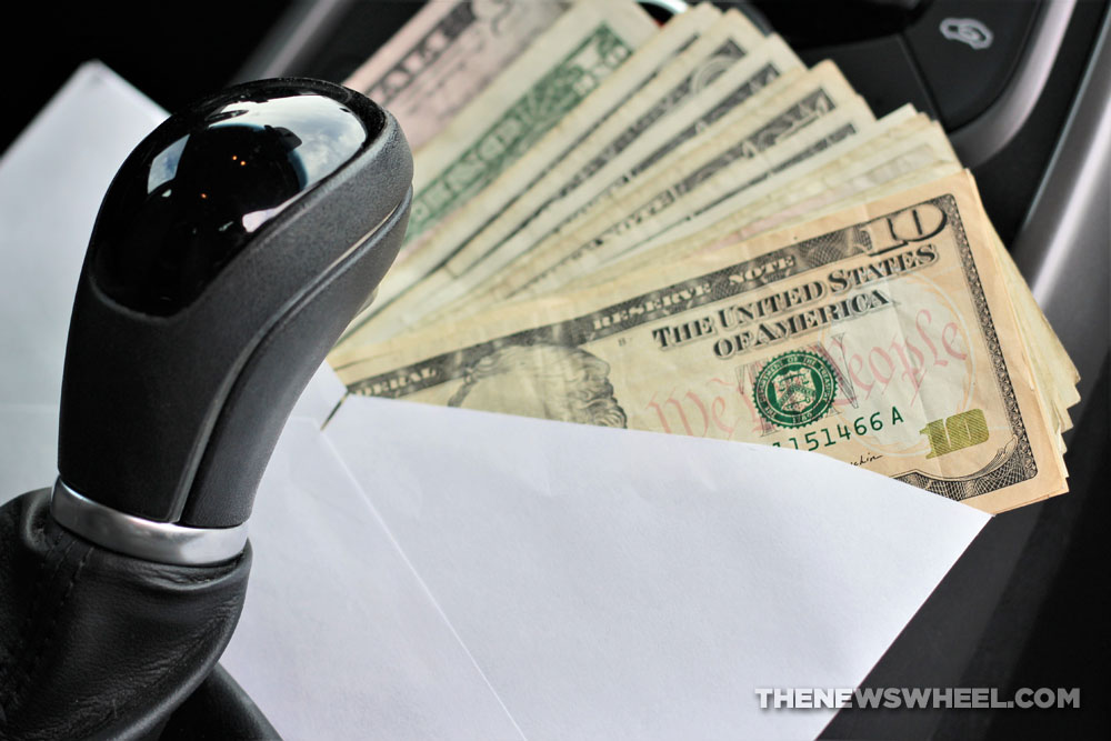 An envelope of U.S. dollars next to an automatic gear shifter.