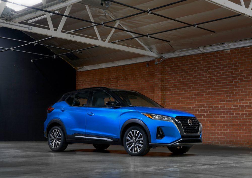 Blue 2021 Nissan Kicks parked inside a garage next to a brick wall