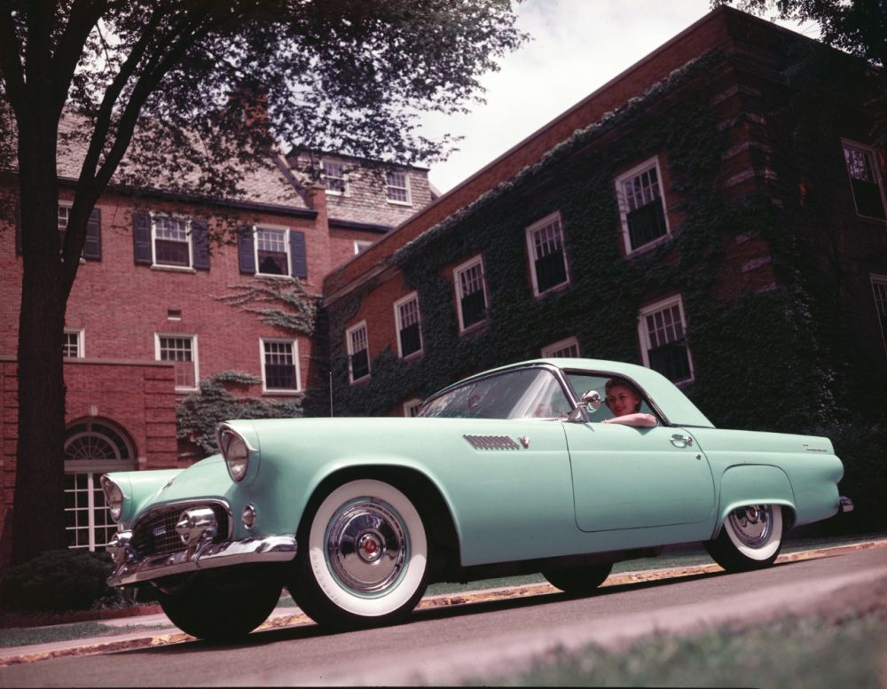 A green 1955 Ford Thunderbird with a woman at the wheel