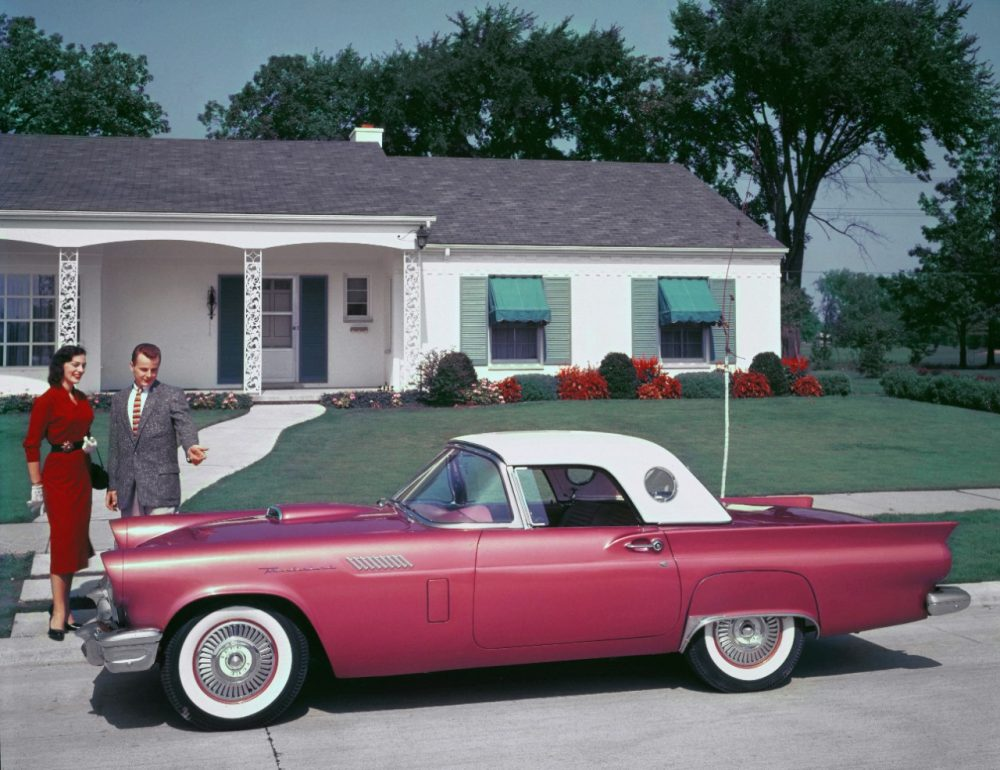 A promotional photo of a couple looking at a red 1957 Ford Thunderbird