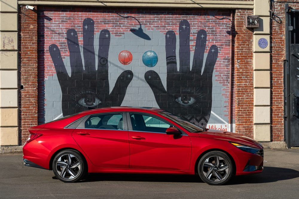Red Hyundai Elantra parked in front of mural