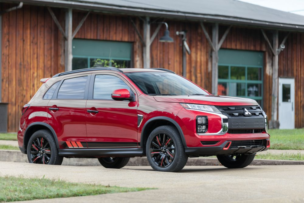 The 2021 Outlander Sport Black Edition in front of a wooden building