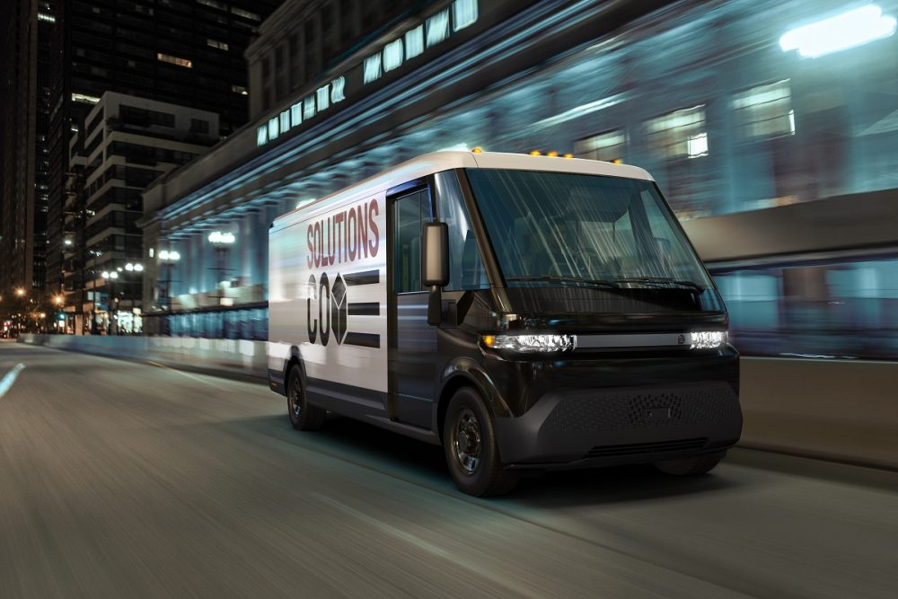 BrightDrop EV600 electric delivery van driving down city street at night