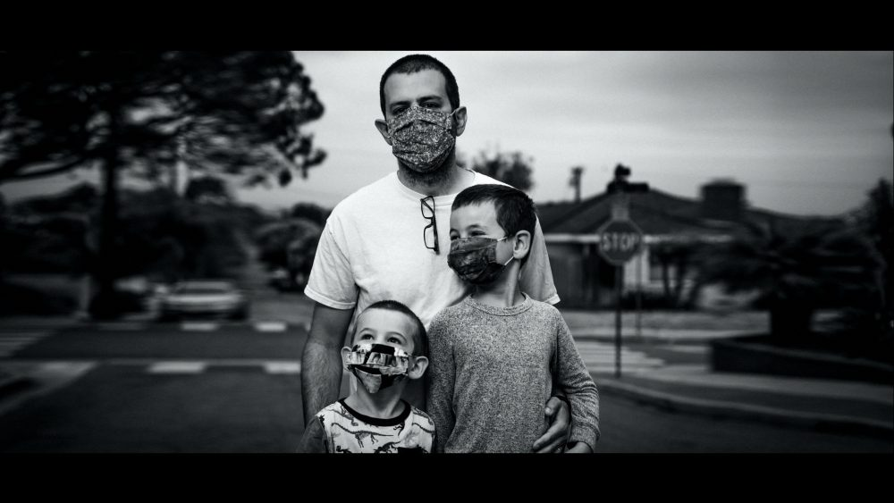 Ford #FinishStrong TV commercial narrated by Bryan Cranston and directed by Peter Berg. This screenshot shows a father and his two children wearing a mask in black and white.