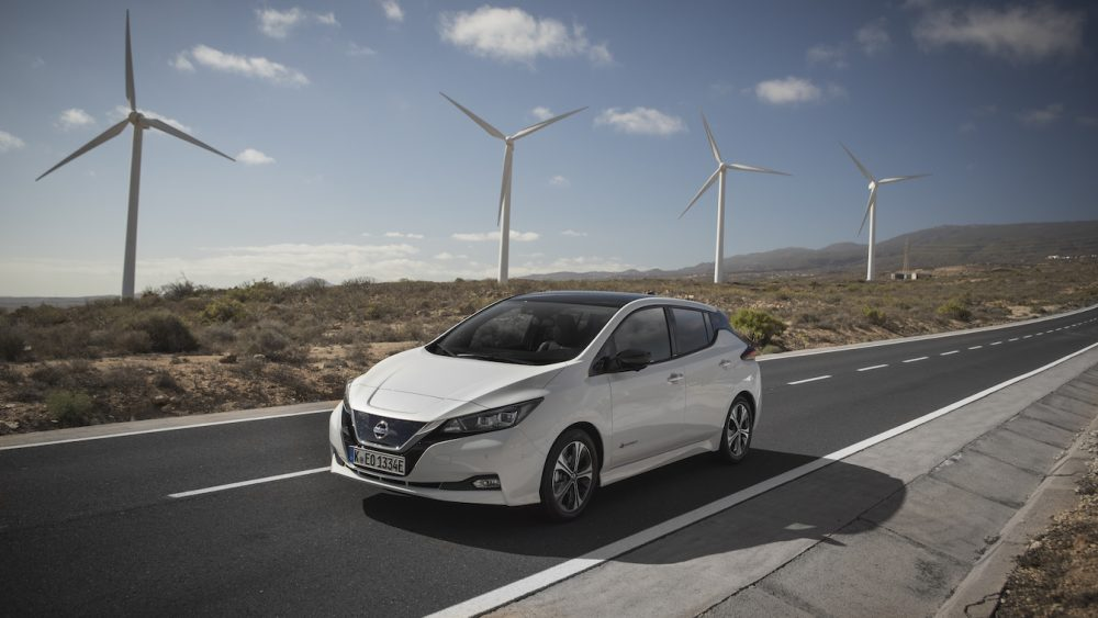 White Nissan Leaf driving on highway with windmills in the background