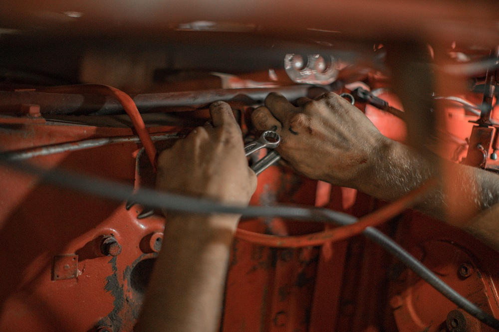 Hands repairing a vehicle intended to evoke RV service technicians