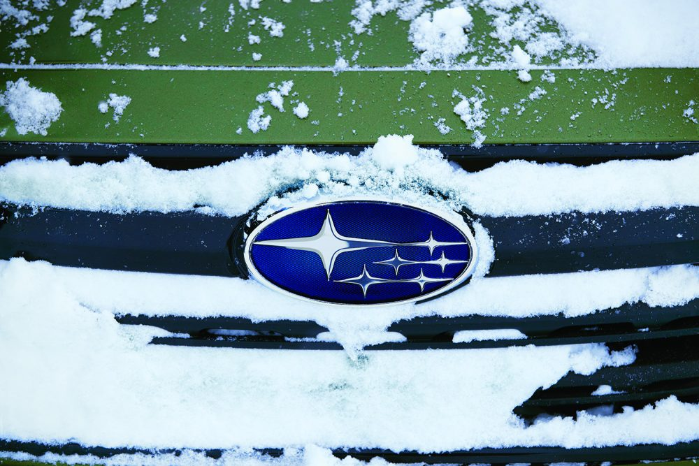 The Subaru logo on a green vehicle covered in a fresh coat of December snow.