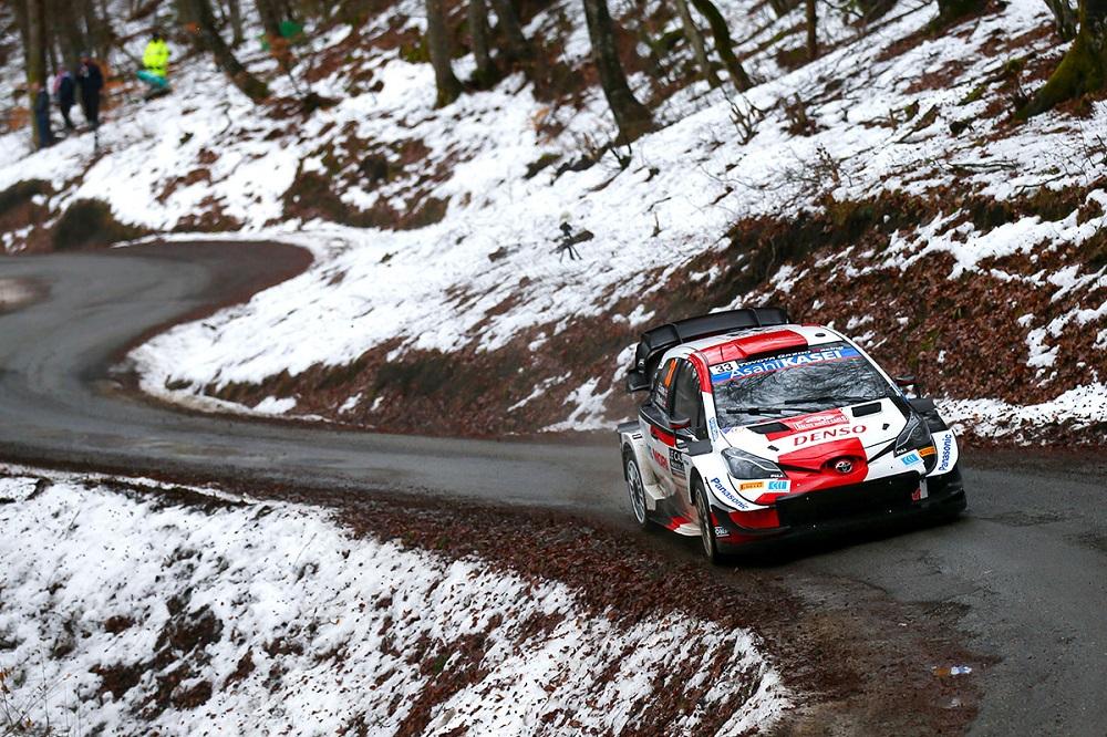Yaris WRC on a damp road winding through snowy landscape