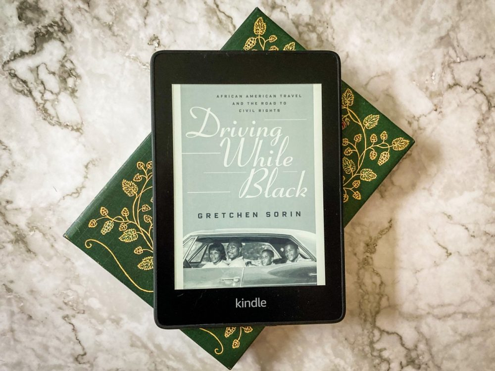 Driving While Black cover displayed on a Kindle Paperwhite as it sits on a green book and a marble counter