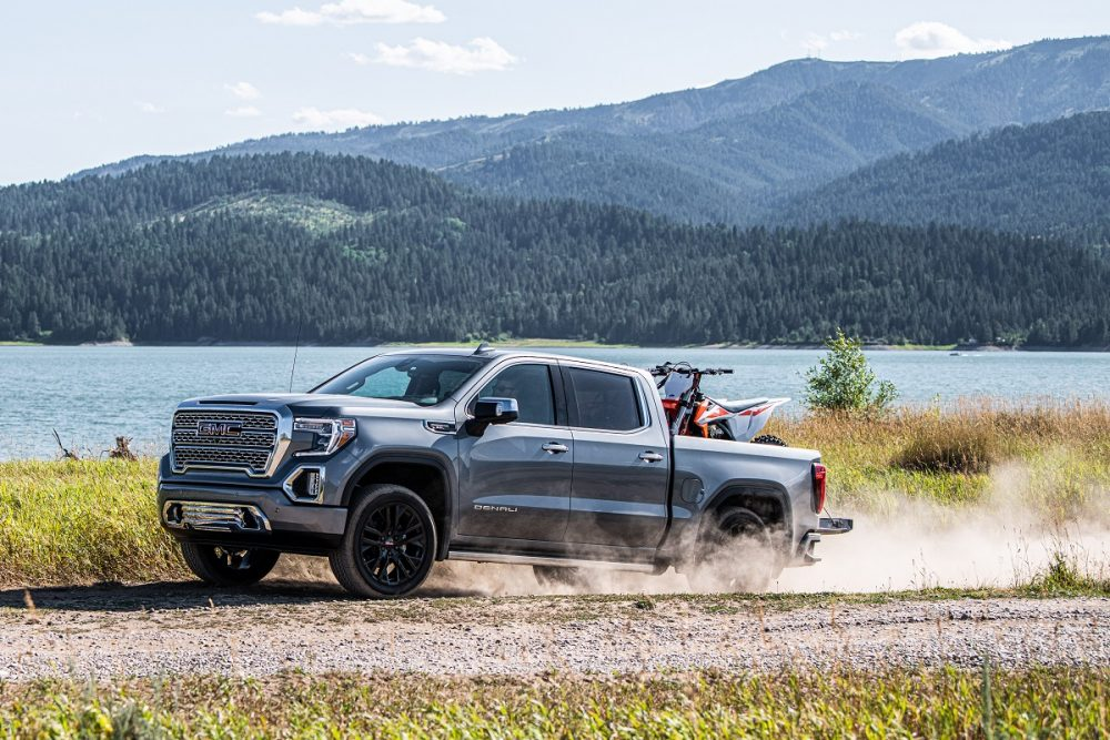 Side view of 2021 GMC Sierra 1500 Denali in action carrying ATV