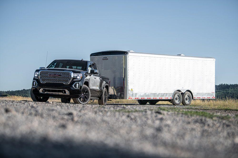 Front side view of 2021 GMC Sierra 1500 Denali pulling large trailer