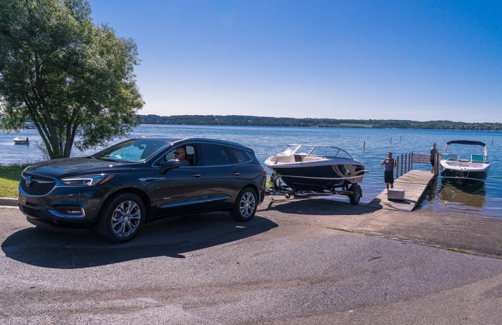 Front side view of Buick Enclave Avenir pulling boat trailer near water