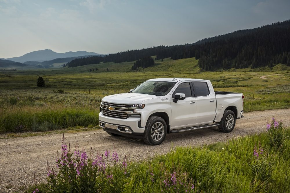 Front side view of Chevrolet Silverado 1500 High Country driving down dirt road
