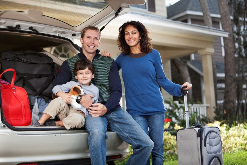 Family of three with luggage in the back of an SUV getting ready to embark on a road trip
