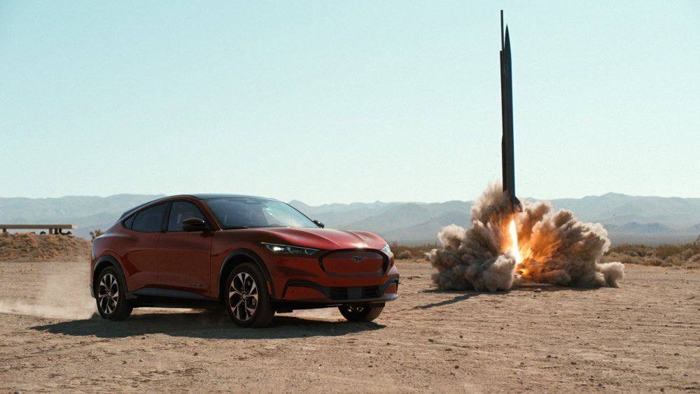 Mustang Mach-E v. Rocket Science - Mustang Mach-E sits next to a rocket launching in the desert
