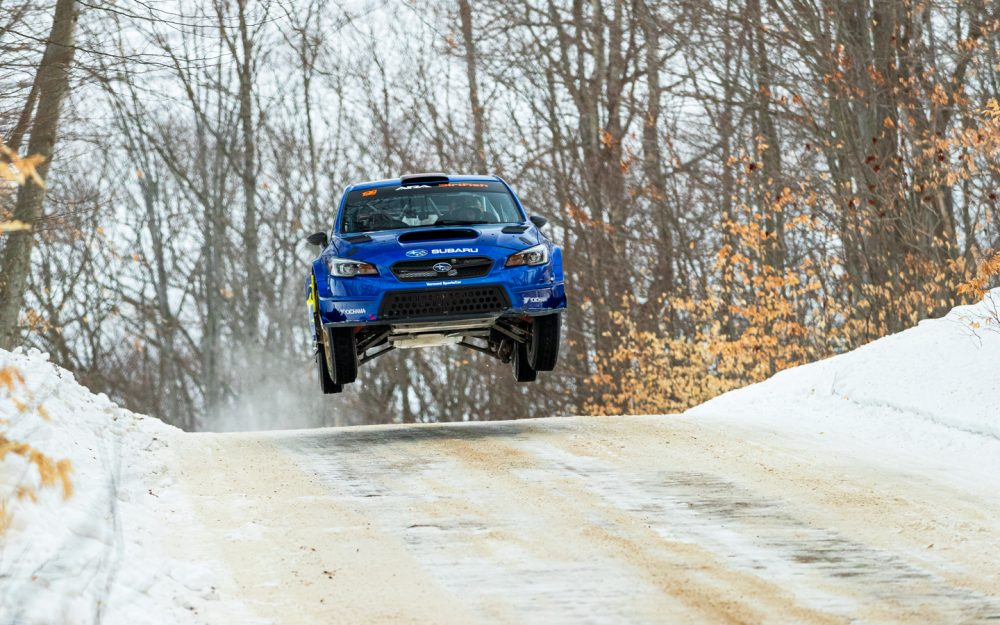 a Subaru WRX STI jumping a hill during the 2021 Sno*Drift Rally race