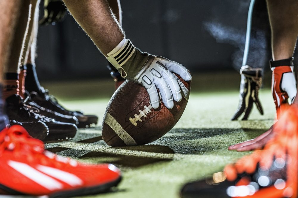 close up of football player hands and ball