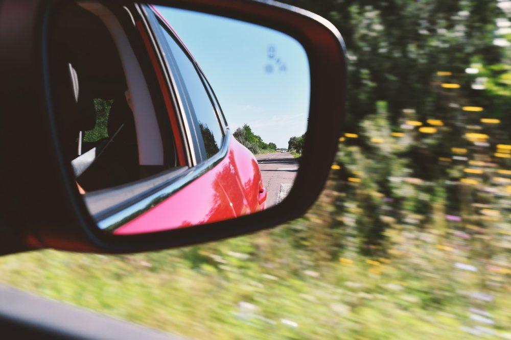 A rear view mirror on a red sedan