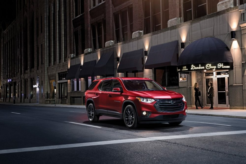 The 2021 Chevrolet Traverse RS driving down the street at night