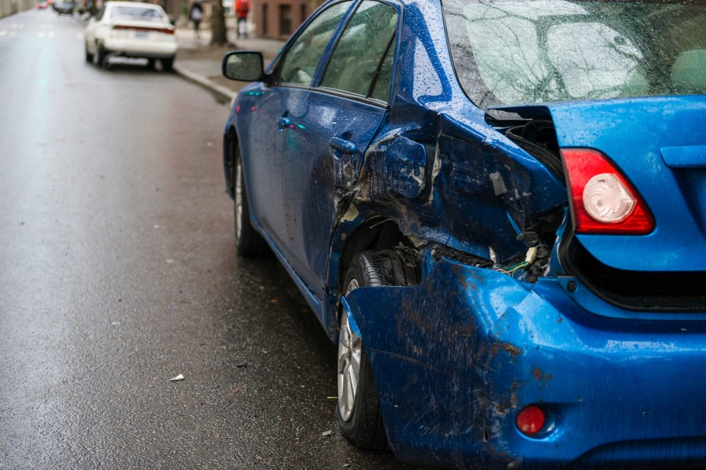 blue sedan with severe collision damage to the rear left-hand side
