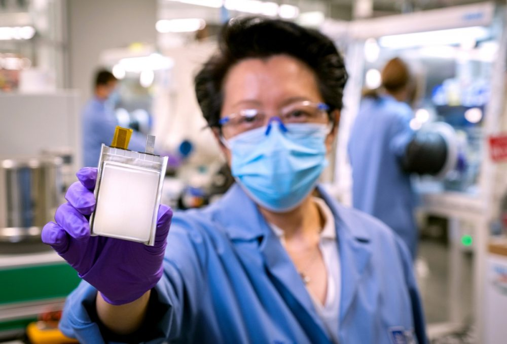 Woman in lab coat and mask holding new GM lithium metal battery