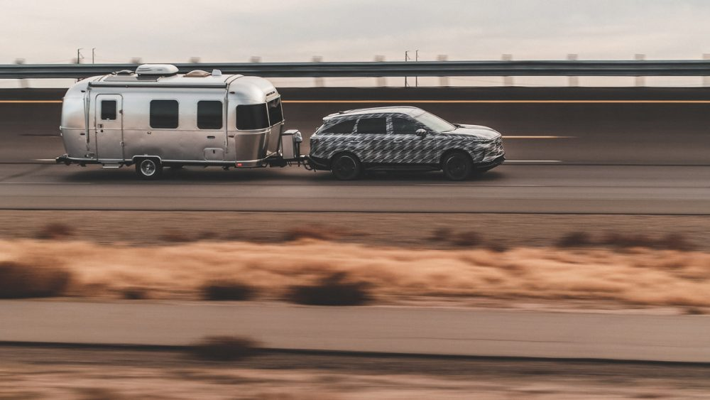 INFINITI QX60 towing an Airstream RV on the road