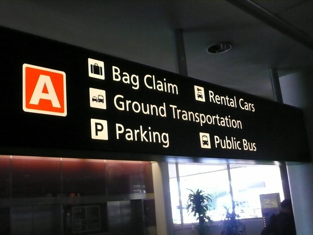 Airport sign directing passengers to the rental car desks