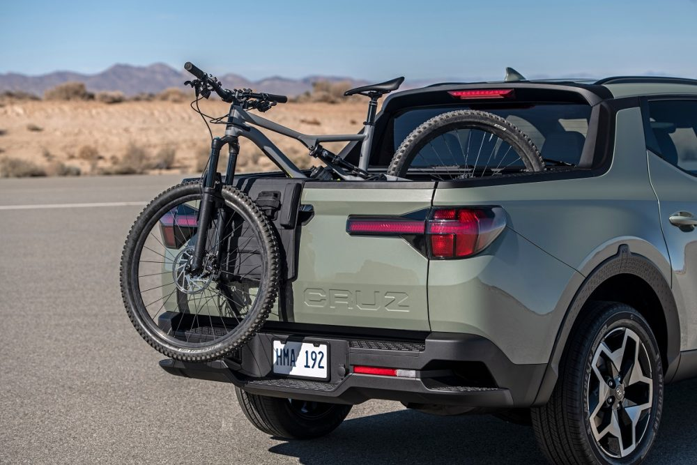 Rear side view of 2022 Hyundai Santa Cruz bed with bicycle hanging out