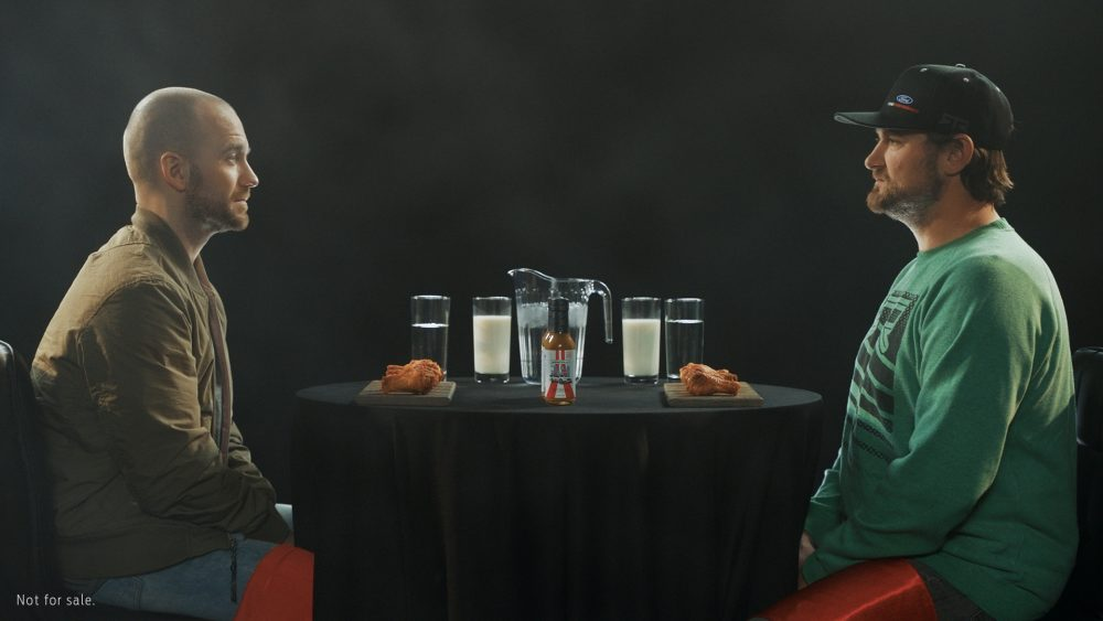 Hot Ones host Sean Evans and Ford Performance driver Vaughn Gittin Jr. prepare to dig into some wings