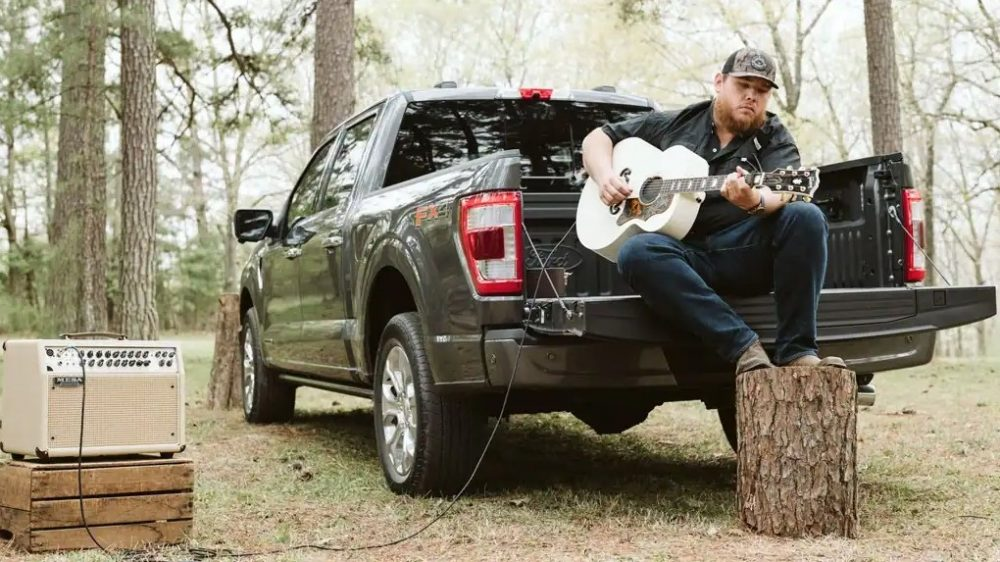 Luke Combs sits in the bed of a 2021 Ford F-150 playing a guitar powered by an amp powered through the truck's Pro Power Onboard built-in generator